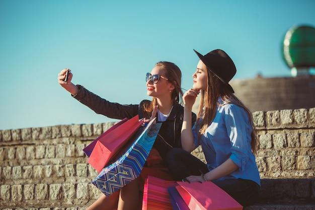 Две девушки гуляют с сумками по улицам города в солнечный день