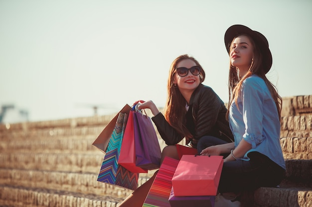 Две девушки гуляют с покупками по улицам города в солнечный день