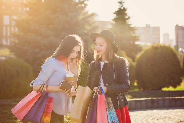 도시의 거리에서 쇼핑을 걷고 두 여자