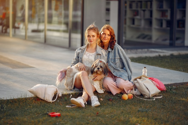 Two girls wallking in a park with a little dog
