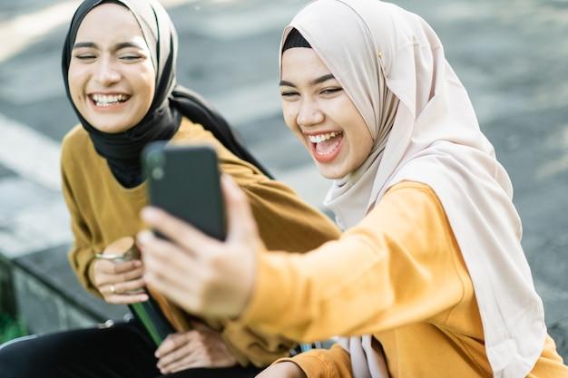 Две девушки в хиджабе смеются, глядя на видео вместе со смартфоном днем в парке