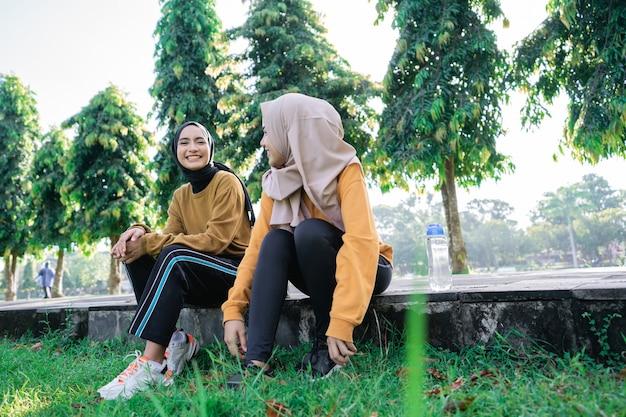 公園で一緒に運動した後、笑顔で午後を楽しむヒジャーブを着た2人の女の子