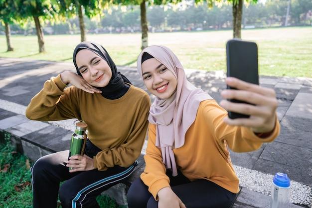 Две девушки в хиджабе улыбаются и держат смартфон во время селфи с камерой смартфона днем в парке