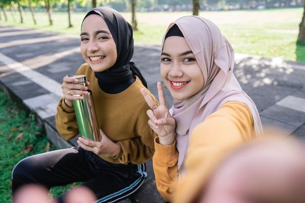 Две девушки в хиджабе улыбаются в камеру смартфона, когда селфи вместе со смартфоном днем в парке