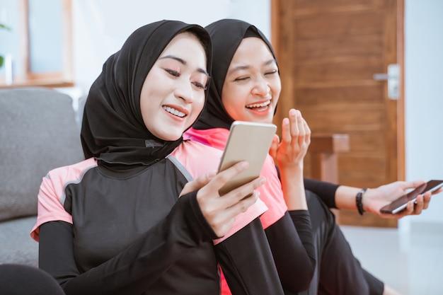 ヒジャーブのスポーツウェアを着た2人の女の子が、家の床に座って携帯電話の画面を見ると笑う