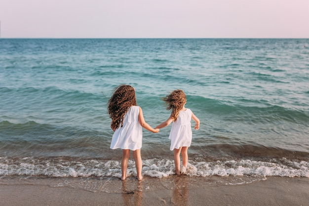 Two girls in white dresses are standing on the beach in sea foam