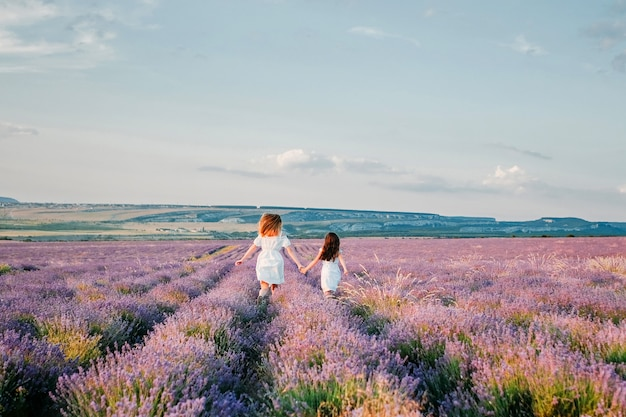 Two girls in white dresses run across a lavender field