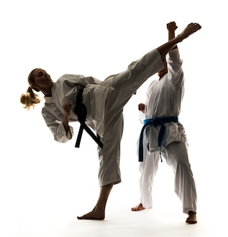 Two girls in white kimonos with black and blue belts, training and practicing karate stands and techniques