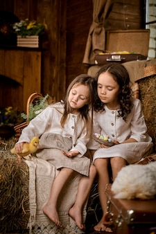 Two girls in white outfits with ducklings in the hay.