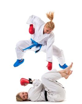 Two girls in white sportswear training fight in boxing gloves