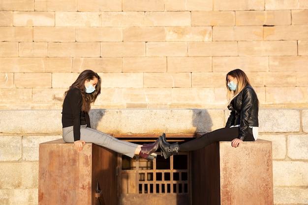 Две девушки в маске поддерживают социальную дистанцию, вытягивая ноги. они на улице.