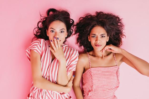 아름다운 황갈색과 검은 곱슬 머리를 가진 두 소녀는 등을 대고 한심한 표정으로 포즈를 취합니다.