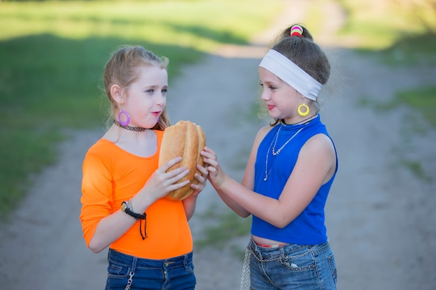Two girls with bright makeup dressed in the style of the nineties are eating a bun