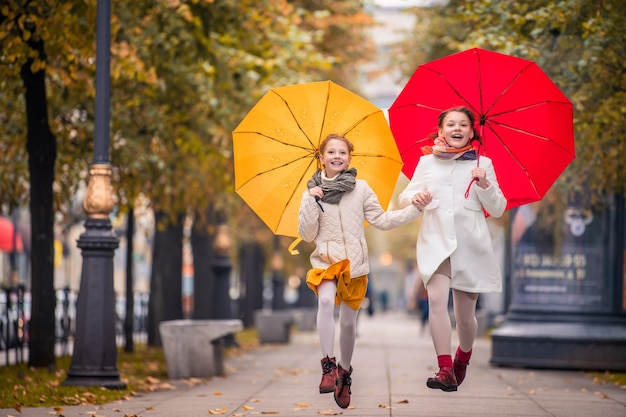 Two girls with bright umbrellas run holding hands on the street of the autumn city.