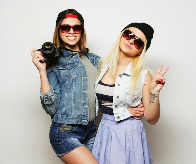 灰色の上に流行に敏感なスタイルのカメラを持つ2人の女の子
