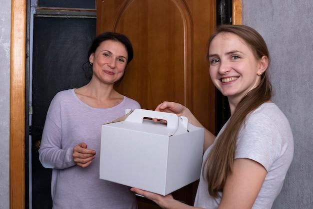 手に段ボール箱を持つ2人の女の子。友達がプレゼントを持って訪ねてきました。ママが娘を訪ねる。