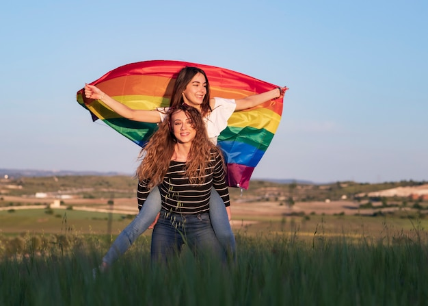 Two girls with gay pride flag happy in nature at sunset