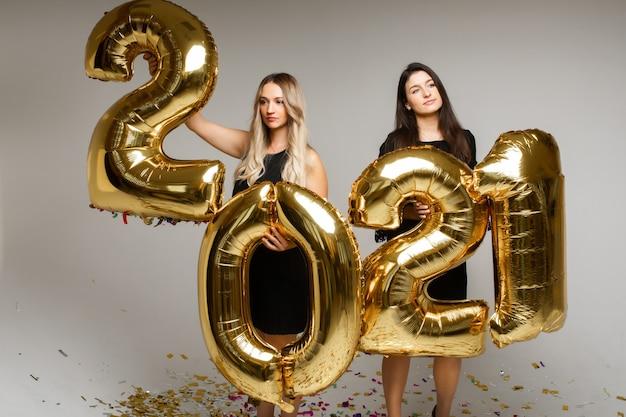 灰色のスタジオの背景に2021年の新年を祝う金色の風船を持つ2人の女の子