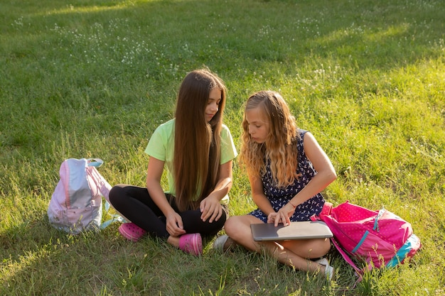 ノートパソコンとブリーフケースを持って宿題をしたり、外の芝生に座って楽しんでいる2人の女の子