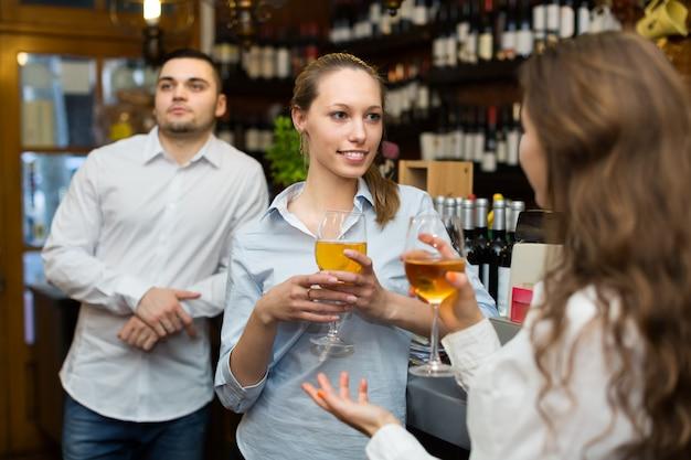 Две девушки с мужчиной в баре