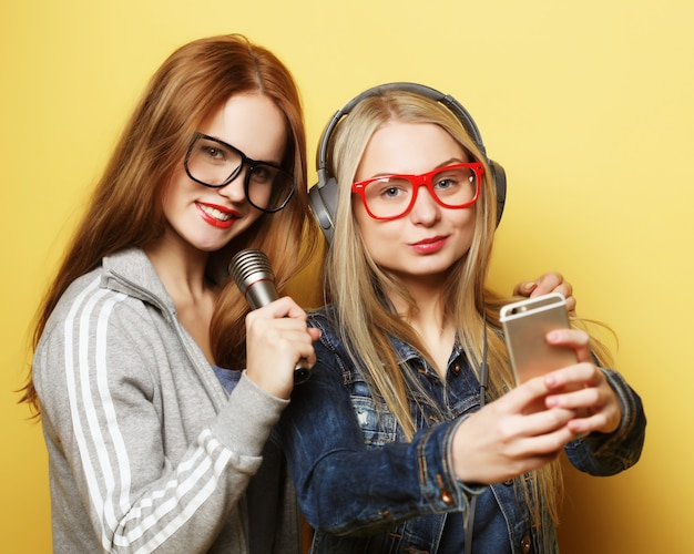 Two  girls with a microphone singing and having fun together, make selfie