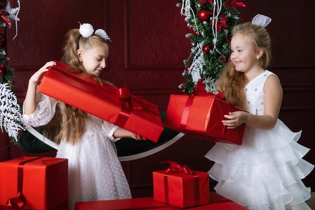 赤いボックスを持つ2人の女の子。クリスマスプレゼント、明けましておめでとうございます。