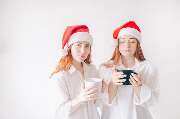 クリスマスの帽子をかぶった赤い髪の2人の女の子がカップを持っています。白い壁に隔離。