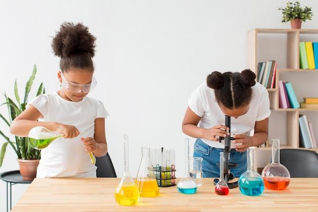 Due ragazze con occhiali di sicurezza che sperimentano la scienza e le pozioni