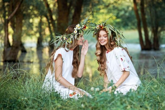 Две девушки с венками из цветов в руках. середина лета. день земли.