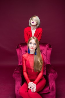 Two girls woman in red clothes siting red chair and red background