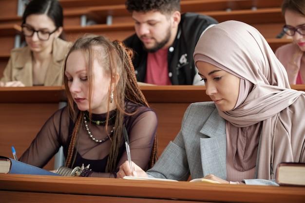 책상 옆에 앉아 수업 시간에 강의 노트를 쓰는 두 소녀