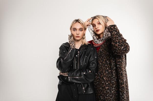 Две гламурные сестры-близнецы в винтажных нарядах леопарда позирует изолированно