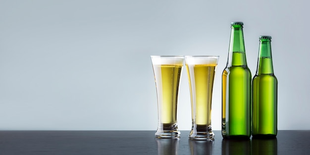 Two glass of beer with bottles on wooden counter with place for text. banner. non alcoholic drink concept.