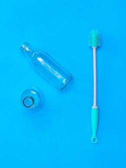 두 개의 유리 병 및 파란색 표면에 세척 브러시. 위생과 청결의 개념.