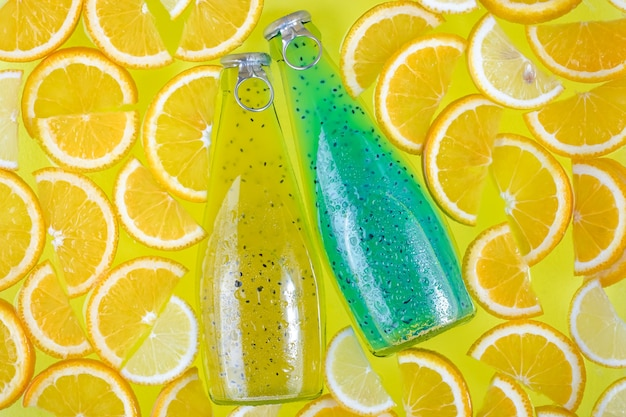 Two glass bottles on a bright tropical citrus background.