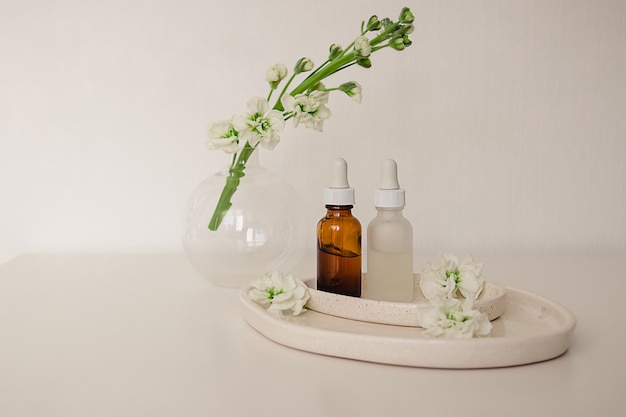 Two glass bottles for cosmetic, natural medicine , essential oil in the  ceramic plates decorated with flowers and a round vase on a white background. eco safe beauty product concept.