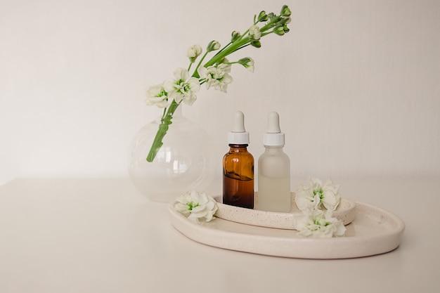 화장품, 자연 의학, 꽃으로 장식 된 세라믹 접시의 에센셜 오일, 흰색 배경에 둥근 꽃병에 대한 두 개의 유리 병. 에코 안전 미용 제품 개념.