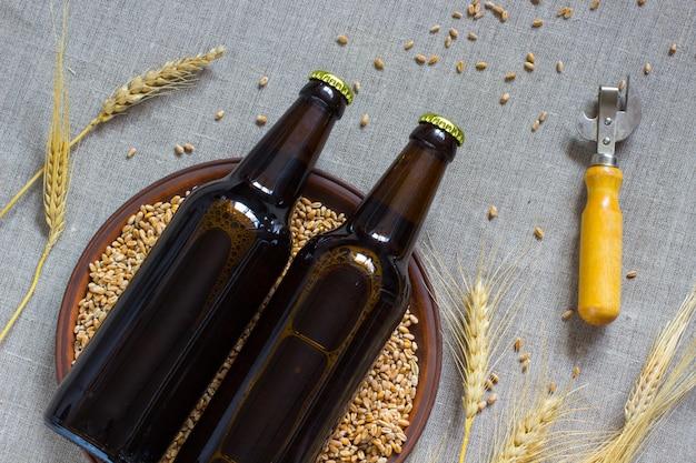Две стеклянные бутылки пива. керамические тарелки с пшеницей. колоски пшеницы.