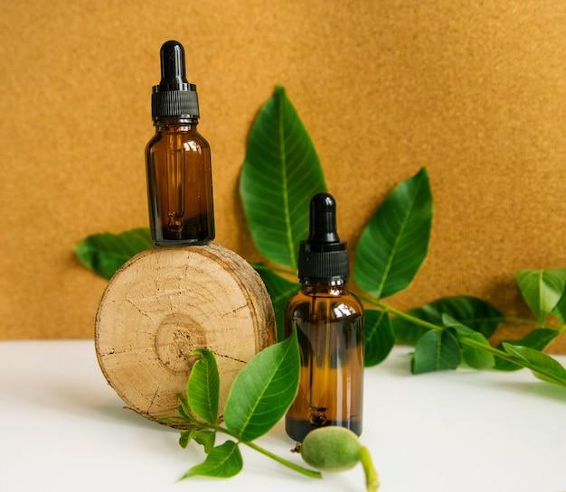 木片にクルミ油のガラス瓶2本。化粧品および医療製品。