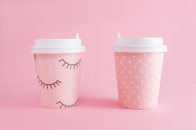 Two glass of coffee take-away on pink pastel background