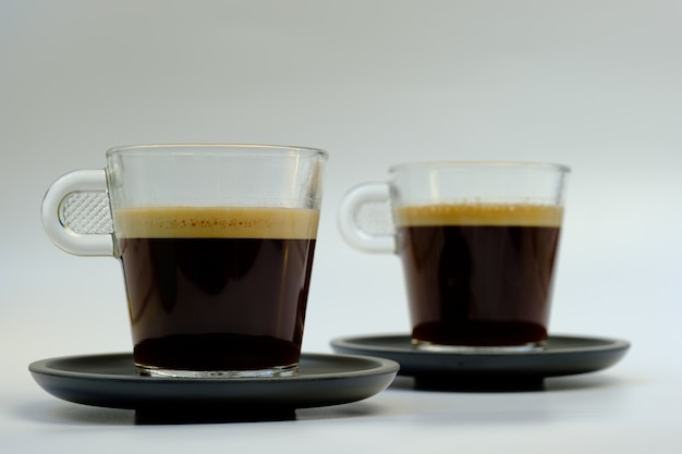 Two glass cups for coffee on two black plates