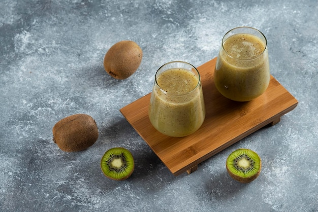 Two glass cups of delicious kiwi juice on wooden board.