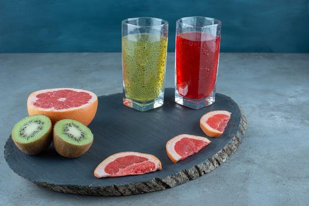 Due tazze di vetro di succhi di frutta freschi con fette di vari frutti.