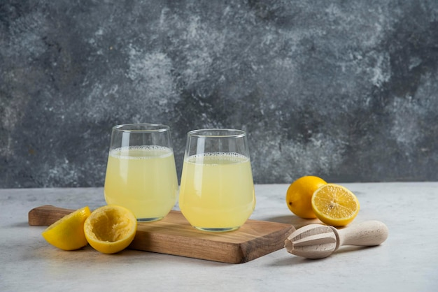 Two glass cups of fresh lemon juice on a wooden board.