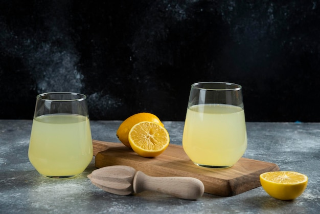 Two glass cups of fresh lemon juice and wooden reamer.