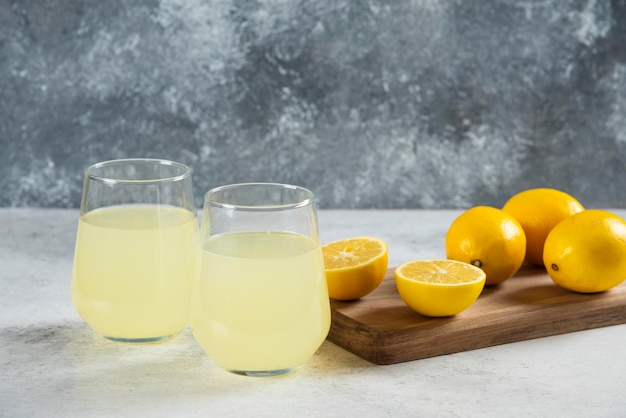 Two glass cups of fresh lemonade on a wooden board.
