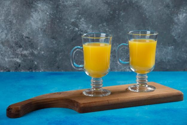 Due tazze di vetro di succo d'arancia fresco su tavola di legno.
