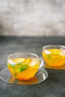 Two glass cups of fuit tea on dark surface