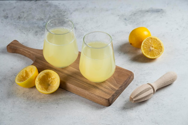 Two glass cups of lemonade on a wooden board.