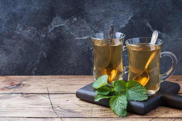 Two glass cups of mint tea on a wooden surface .